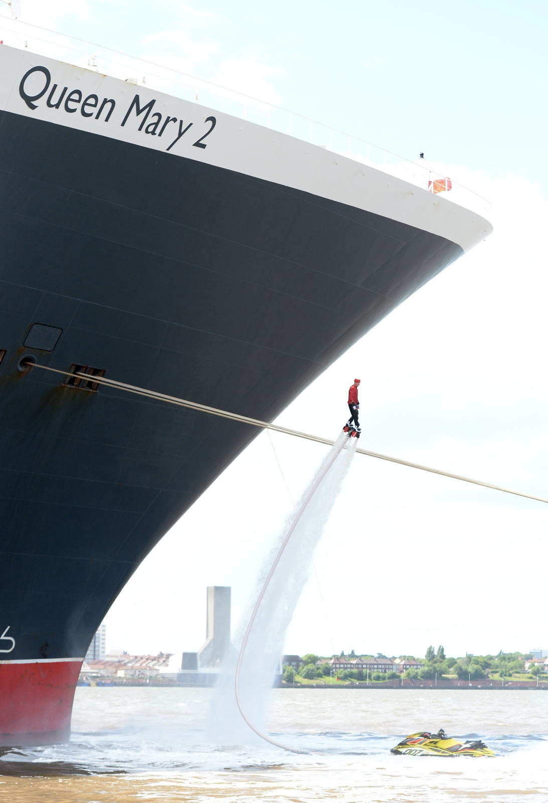 Flyboarder rises high next to Queen Mary 2