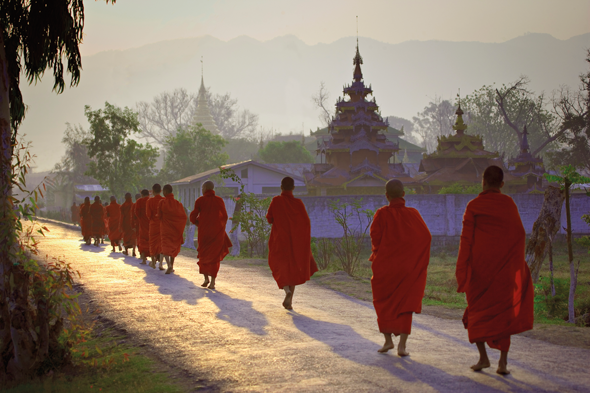 Buddhist monks dressed in their red robes walking down a road. Credit Getty Images
