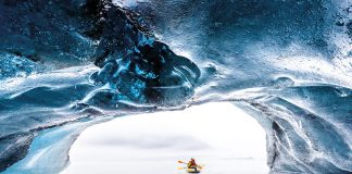 Tourists kayaking out of the brilliant blue ice cave, Valdez, Alaska