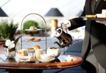 Butler serves tea on board an upgraded cruise