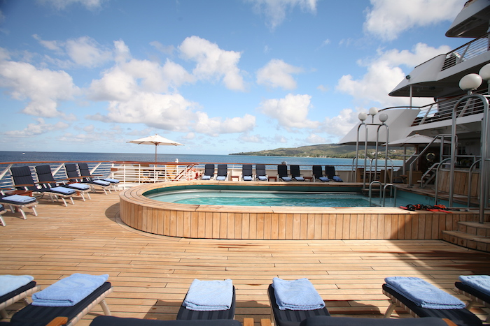 sun loungers line up on teak decks next to pool on SeaDream Spain cruise