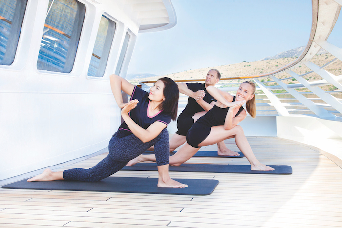 three guests do yoga on the deck of SeaDream I