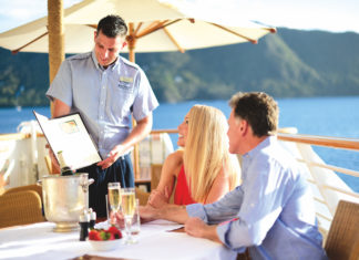 couple dining al fresco on board a cruise ship being served by a crew member