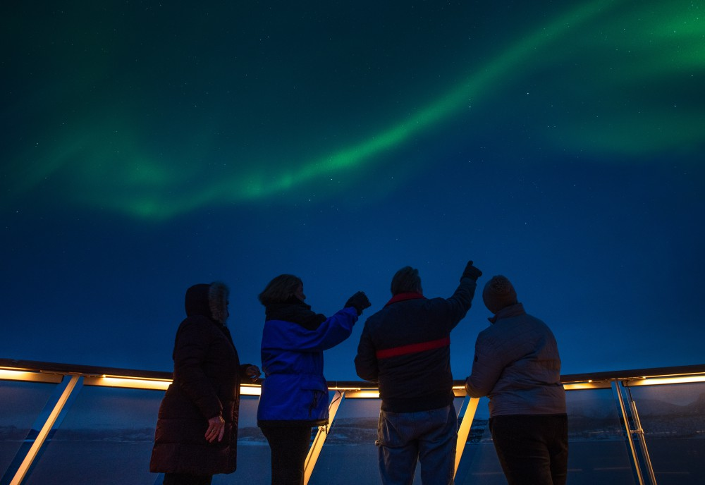 Guests on a Viking Northern Lights cruises take in the colourful night skies